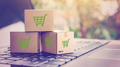 Symbolbild eCommerce: Einkaufswagen auf Würfeln