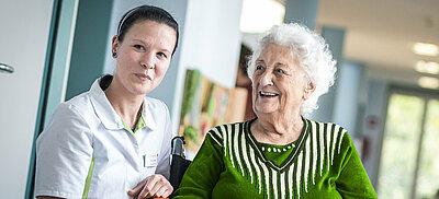 Mitarbeiterin in der Pflege mit Patientin