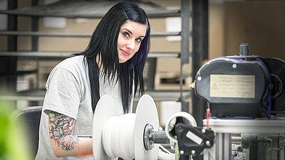 Quereinsteigerin bei der Arbeit an einer Maschine