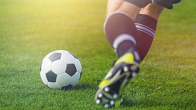 Fußballspieler kickt Ball